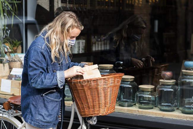 Junge blonde Frau mit Gesichtsmaske und Fahrrad steht vor dem abfallfreien Vollsortimenter. — Stockfoto