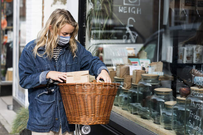 Young blond woman wearing face mask with bicycle, standing outside waste free wholefood store. — Stock Photo