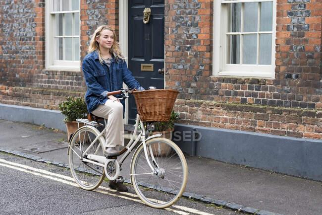Jeune femme blonde faisant du vélo dans une rue du village. — Photo de stock