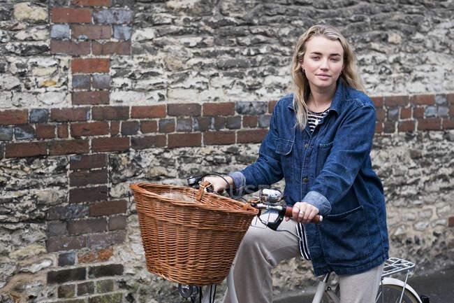 Молодая блондинка на велосипеде с корзиной, смотрит в камеру. — стоковое фото