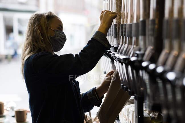 Giovane donna bionda con maschera viso, shopping in deposito di cibo intero senza rifiuti. — Foto stock