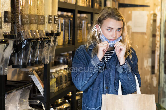 Junge blonde Frau mit Gesichtsmaske shoppt in abfallfreiem Vollwertladen. — Stockfoto