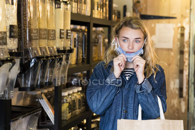 Jeune femme blonde portant un masque facial, faisant du shopping dans un magasin d'aliments complets sans déchets. — Photo de stock