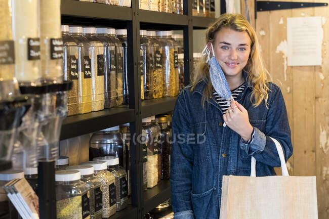 Jovem loira usando máscara facial, fazendo compras em loja de comida integral livre de resíduos. — Fotografia de Stock