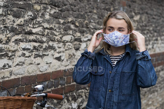 Young blond woman standing outdoors, putting on face mask. — Stock Photo