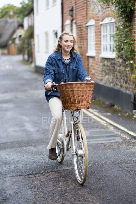 Young blond woman cycling down a village street. — Stock Photo