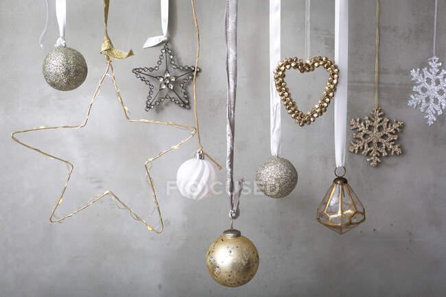 Décorations de Noël, boules d'argent, blanc et or sur rubans sur fond gris. — Photo de stock