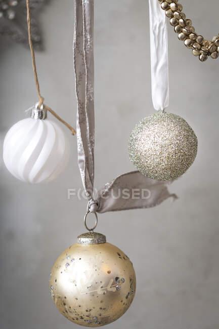 Decorazioni natalizie, palline d'argento, bianco e oro su nastri su fondo grigio. — Foto stock