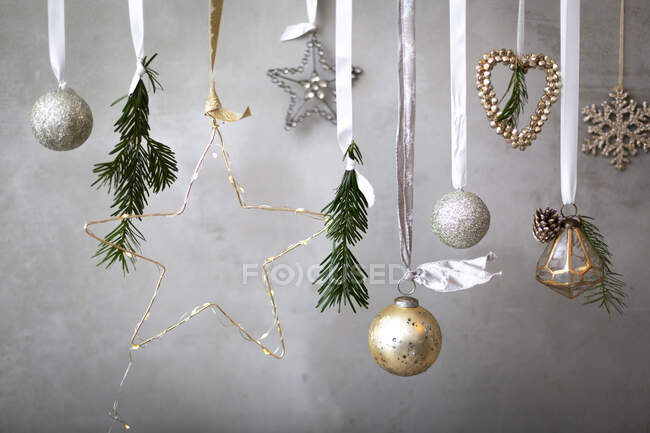 Christmas decorations, silver, white and gold baubles on ribbons on grey background. — Stock Photo