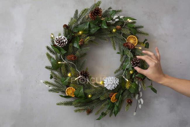 Addobbi natalizi, primo piano della persona che decora la corona natalizia con ornamenti. — Foto stock