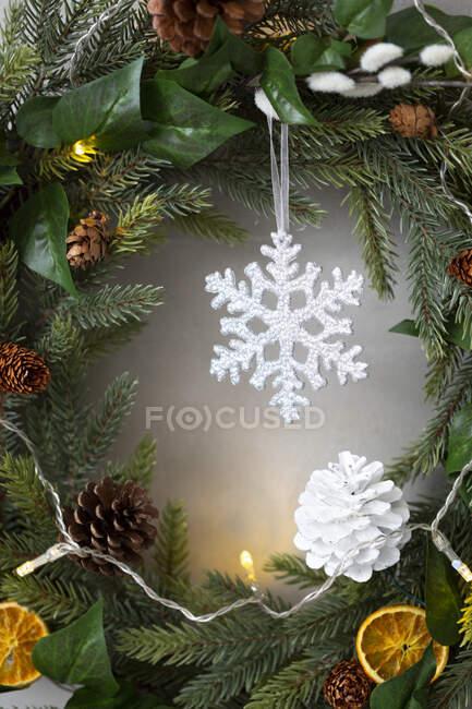 Addobbi natalizi, primo piano di pigna bianca e fiocco di neve sulla corona di Natale. — Foto stock