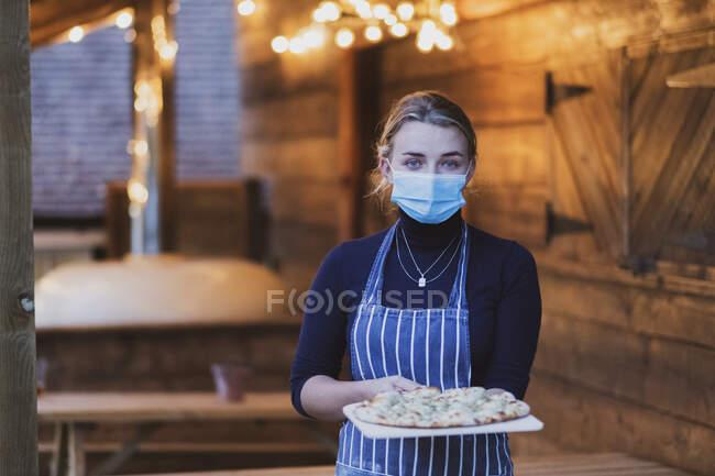 Kellnerin in Schürze und Gesichtsmaske hält frische Pizza auf einem Brett — Stockfoto