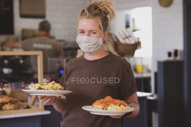 Cameriera bionda che indossa maschera viso lavorando in un caffè, portando piatti di cibo. — Foto stock