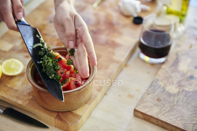 Нарезанный базилик добавляется в томатный салат, обрезанный кадр — стоковое фото