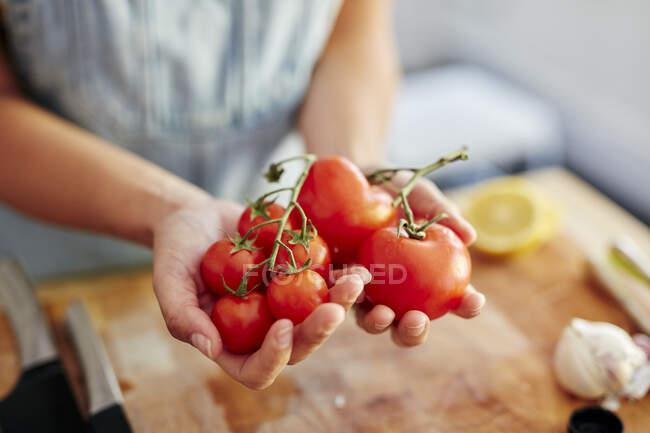 Mujer sosteniendo tomates orgánicos de diferentes tamaños en la cocina - foto de stock