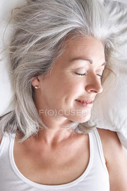 Зрелая привлекательная белая женщина спит на белых простынях, голове и плечах — стоковое фото