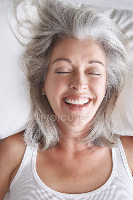 Mature attractive Caucasian woman lying down on white sheets, eyes closed, laughing. — Stock Photo