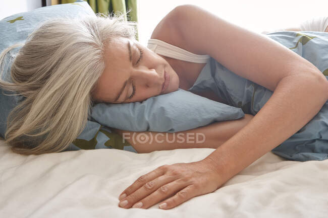 A mature Caucasian woman lying in bed and sleeping — Stock Photo