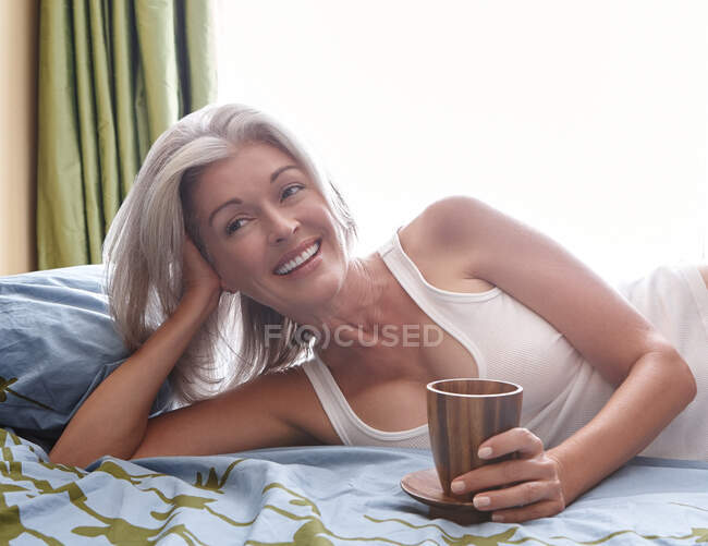 Portrait of attractive vivacious mature Caucasian woman with silver hair lying on bed — Stock Photo