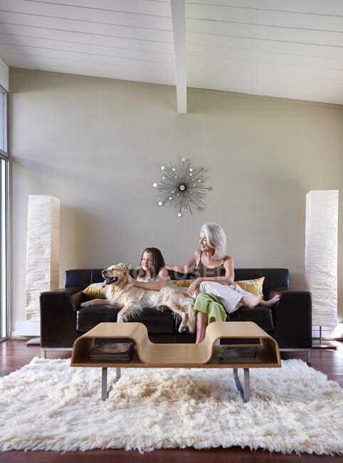 Зрелая женщина и подросток, мать и дочь на диване со своей золотой собакой-ретривером. — стоковое фото