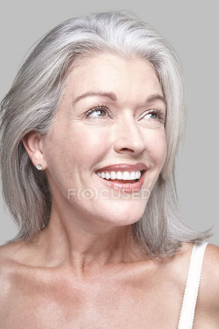Attractive mature Caucasian woman with silver grey hair in a white tank top, bare shoulders. — Stock Photo