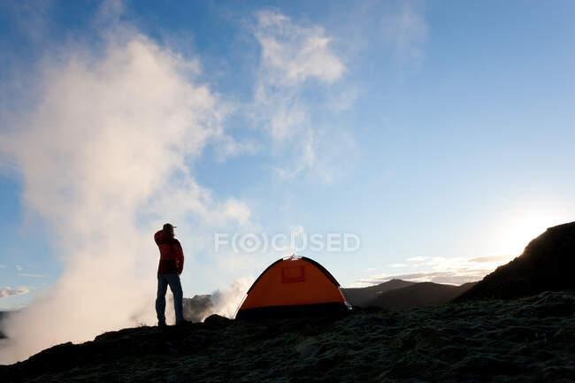Femme debout près de la tente au lever du soleil, Islande — Photo de stock