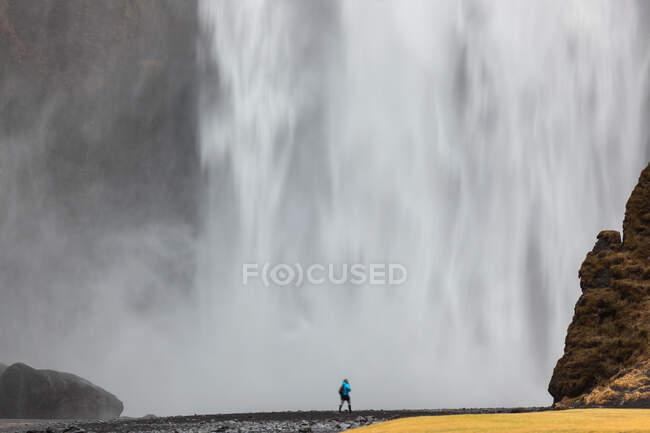 Cascada de Skogafoss, hombre de pie frente a una enorme pared de agua - foto de stock