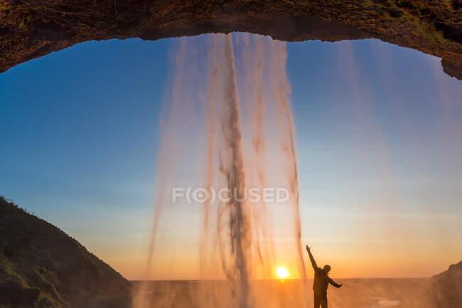 Homme derrière Seljalandsfoss Cascade, Islande du Sud, Islande — Photo de stock
