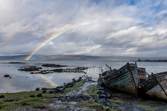 Rainbow and beached old wooden fishing boats on shore at Salen — Stock Photo