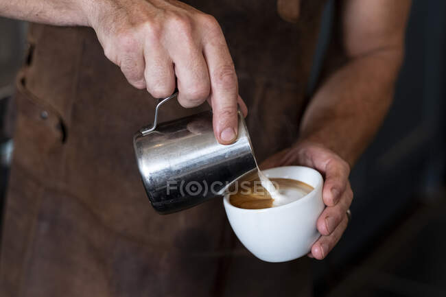 Close up of barista wearing brown apron pouring cappuccino. — Stock Photo