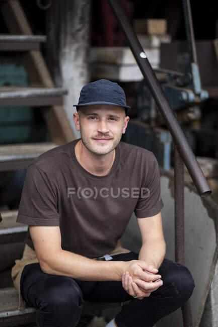 Varón barista con gorra de béisbol negra y máscara facial sentado en las escaleras al aire libre, sonriendo a la cámara. - foto de stock