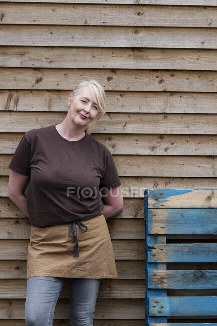 Portrait of waitress wearing brown apron, leaning against wall, smiling. — Stock Photo