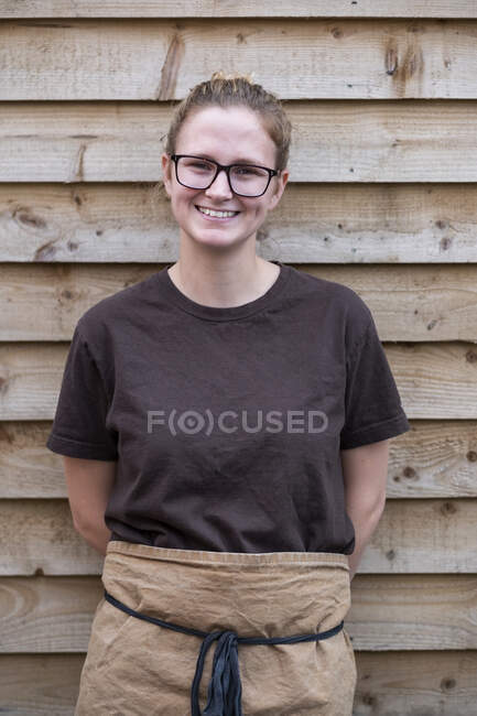 Portrait of female barista with blond hair and glasses, wearing brown apron, leaning against wooden wall, smiling at camera. — Stock Photo