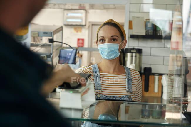 Donna in maschera dietro il bancone del caffè con schermo di sicurezza, che offre un terminale di pagamento senza contatto a un cliente — Foto stock