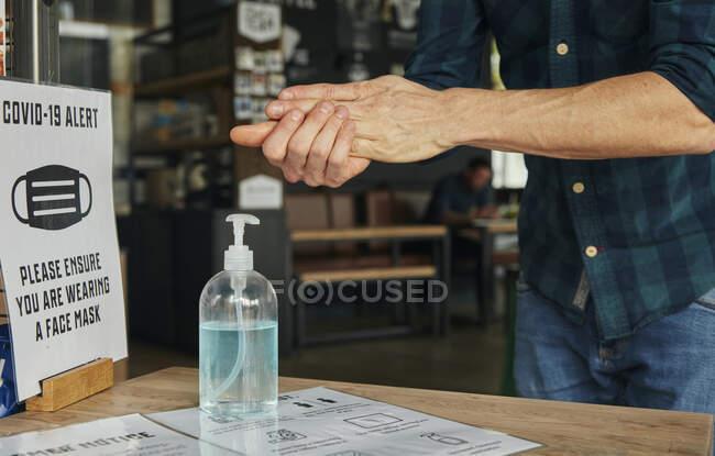 Мужчина массирует руки с помощью дезинфицирующего средства для рук в ресторане — стоковое фото