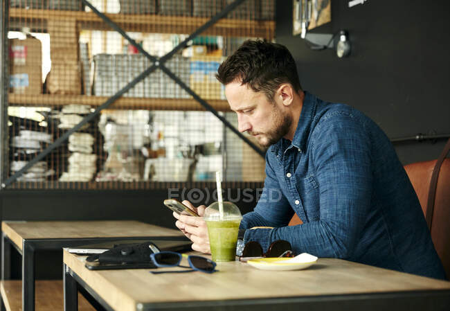 Man sitting alone at table with laptop and juice drink in cafe using smart phone — Stock Photo