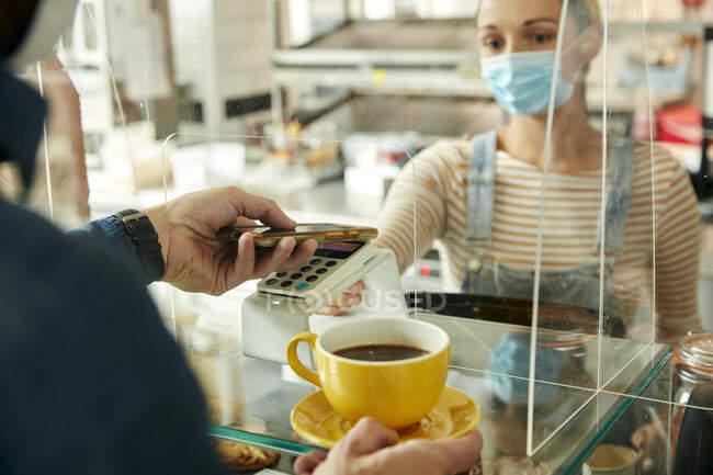 Mulher em uma máscara facial atrás do balcão de café com tela de segurança, oferecendo um terminal de pagamento sem contato para um cliente — Fotografia de Stock