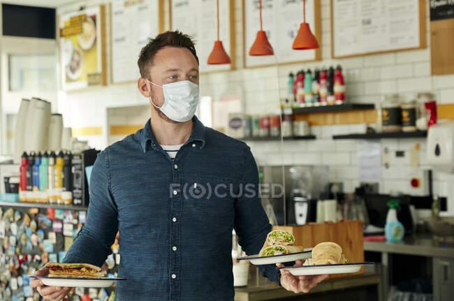 Офіціант у масці тримає дві тарілки їжі для клієнтів. — стокове фото