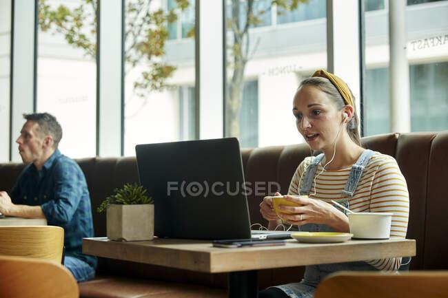 Frau sitzt in einem Café und interagiert während eines Online-Anrufs mit einem Laptop — Stockfoto