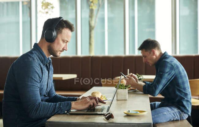 Deux hommes assis dans un café, travaillant à distance avec un ordinateur portable et un téléphone intelligent — Photo de stock