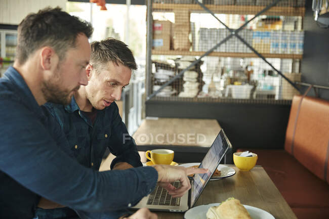 Two men sitting in a cafe using a laptop sharing a screen — Stock Photo