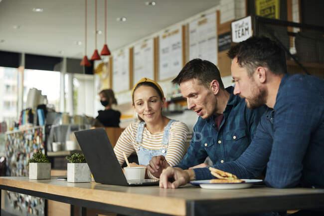 Двоє чоловіків і жінка сидять у кафе і дивляться на ноутбук. — стокове фото