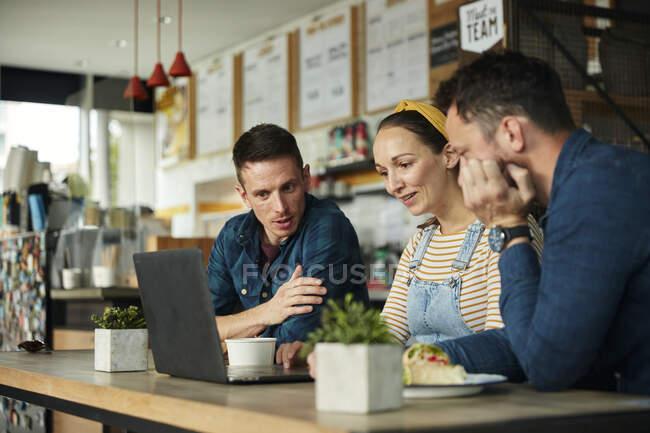 Zwei Männer und eine Frau sitzen in einem Café und schauen auf einen Laptop — Stockfoto