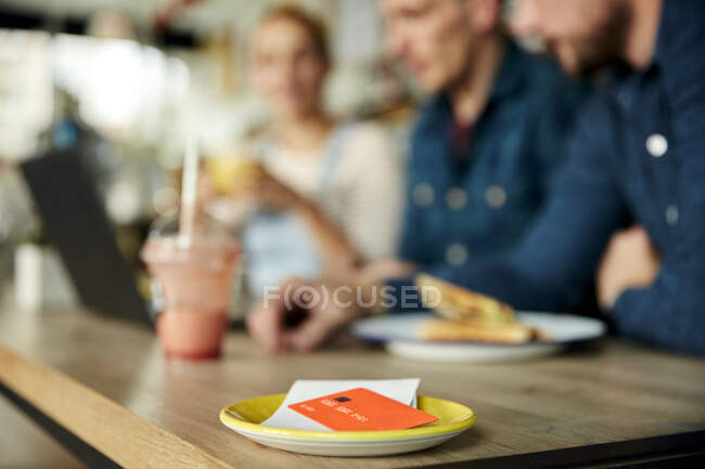 People at a cafe table, a saucer with till receipt and credit card. — Stock Photo