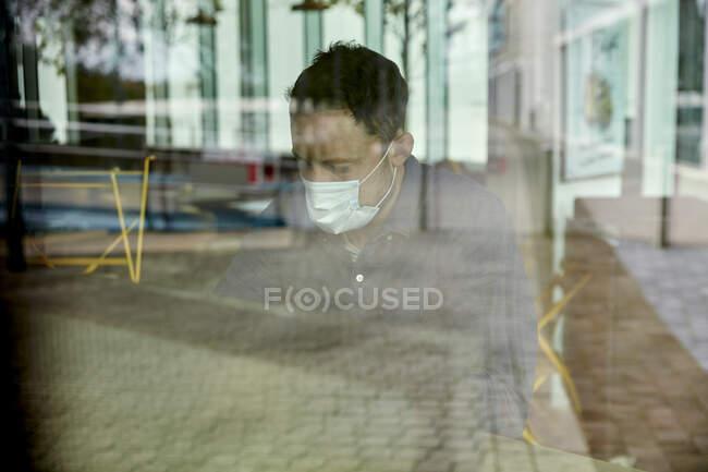 Homem com uma máscara facial sentado em uma mesa de café, vista através de uma janela — Fotografia de Stock