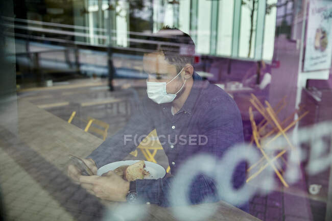 Man in a face mask sitting at a cafe table using a mobile phone, view through a window — Stock Photo