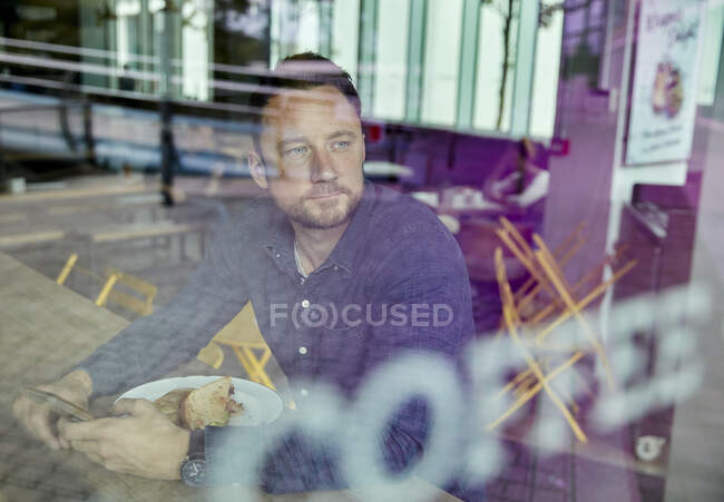 Man in a face mask sitting at a cafe table, view through a window — Stock Photo