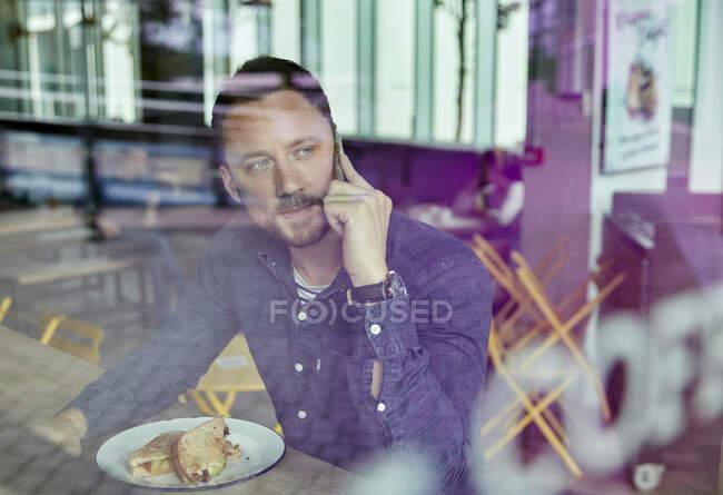 Homem em uma máscara facial sentado em uma mesa de café usando um telefone celular, vista através de uma janela — Fotografia de Stock