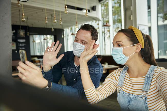 Duas pessoas usando máscaras faciais, usando um telefone inteligente, acenando durante uma chamada de face time. — Fotografia de Stock