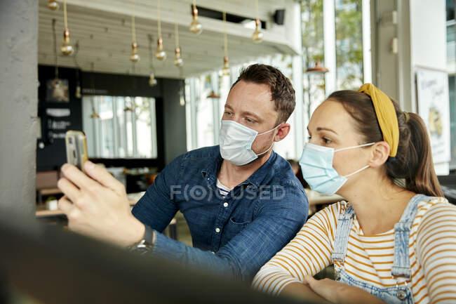 Двоє людей у масках обличчя, за допомогою смартфона махають обличчям під час дзвінка.. — стокове фото